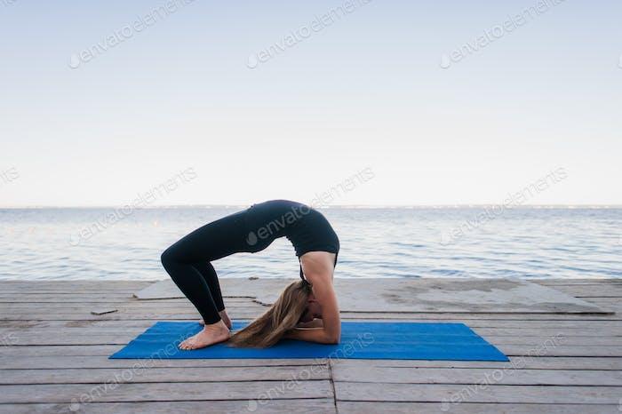 Schöne sportliche Passform blonde junge Frau in schwarzer Sportbekleidung arbeiten draußen auf Holzponton auf