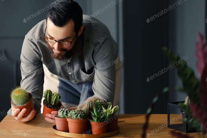 Happy hipster whose hobby is gardening looking at cacti at woode