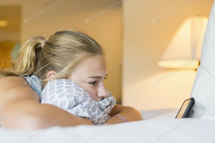 13 year old girl lying on hotel room bed looking at smart phone