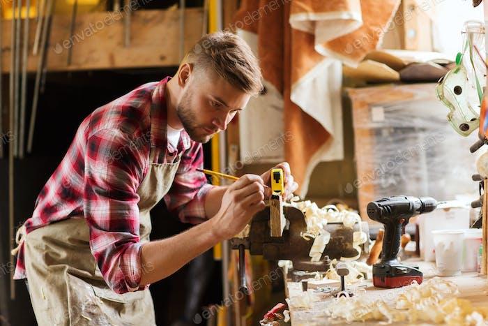 carpenter with ruler measuring plank at workshop