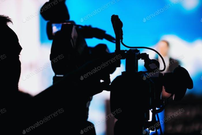Cameraman Recording Speaker bei Medienpressekonferenz