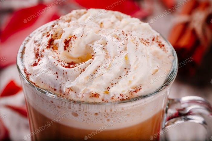 pumpkin latte with whipped cream in a glass jar closeup