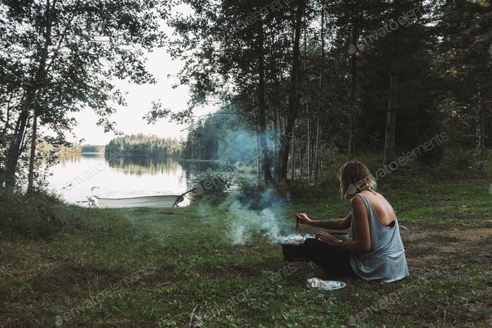 Young woman barbecuing near lake