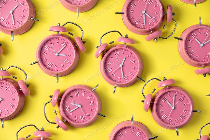 Creative layout of pink alarm clock's on pastel yellow background. Minimal concept.