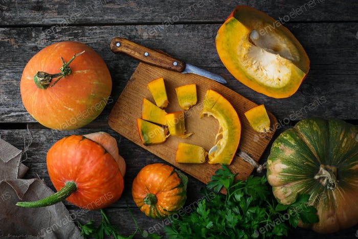 Raw chopped pumpkin on wooden background