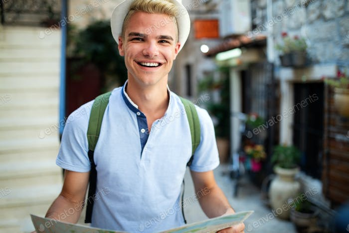 Happy young man smiling and traveling at summer vacation