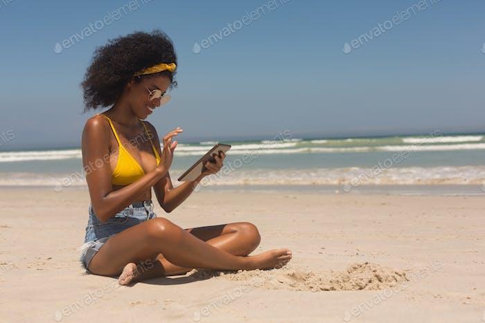 Woman in yellow bikini and sunglasses using digital tablet sitting on the beach