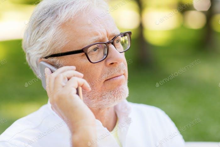 sad senior man in glasses calling on smartphone