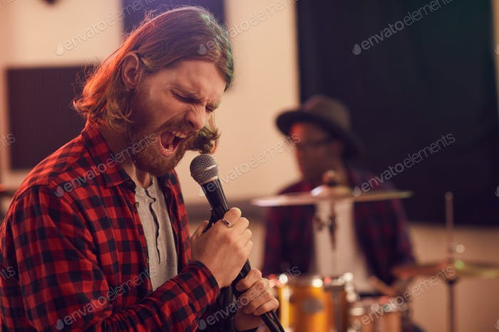 Bearded Young Man Screaming to Microphone