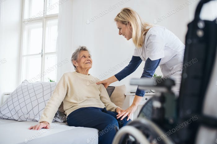 A health visitor talking to a senior woman sitting on bed at home.