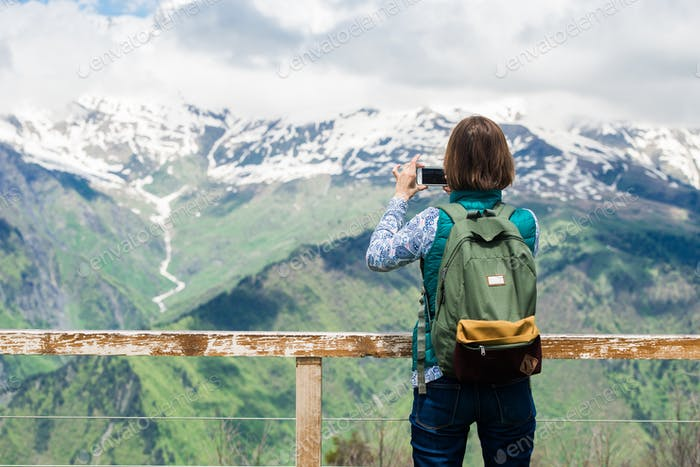 Pretty young woman girl stay on mountain top and taking picture with smart phone over beautiful