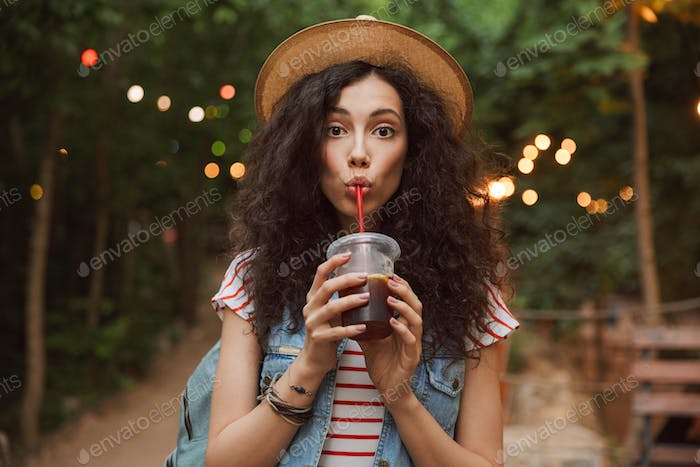 Photo of lovely summer woman 18-20 wearing straw hat, looking at