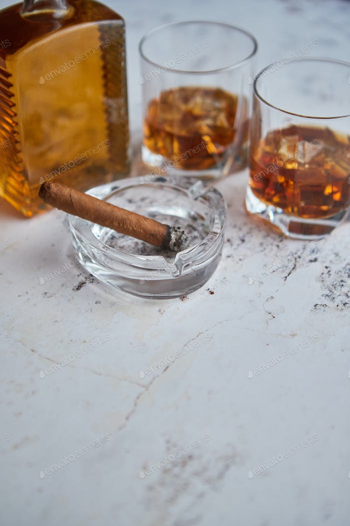 Bottle and glasses of brandy or wiskey and nice big cuban cigar