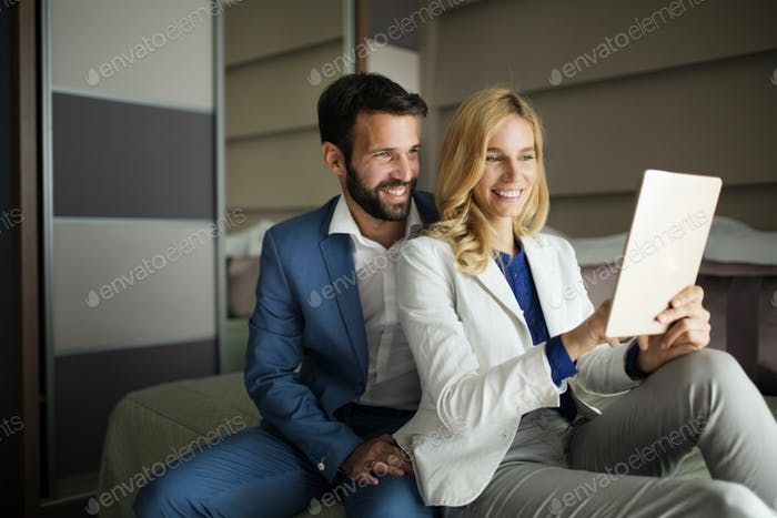 Businessman and businesswoman sitting on bed and using tablet