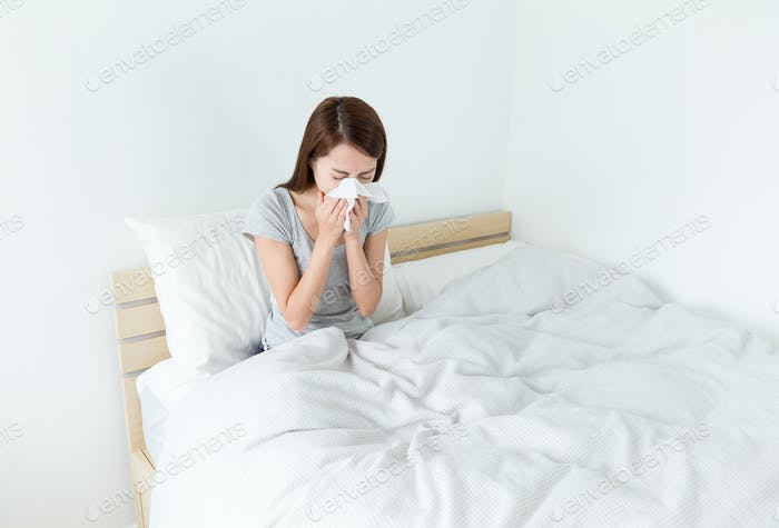 Woman sneeze on the bed
