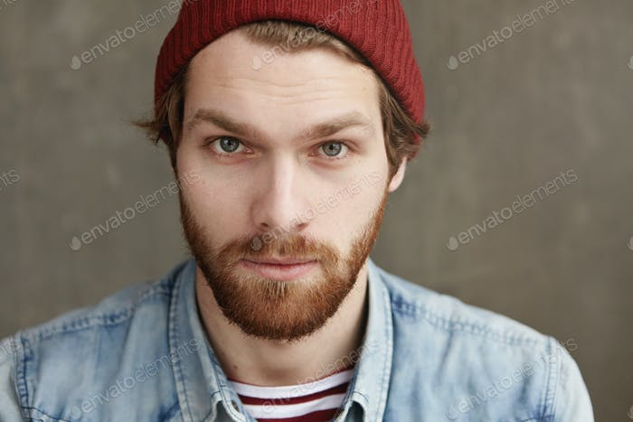 Portrait of handsome young hipster male of European appearance posing indoors. Close up shot of styl