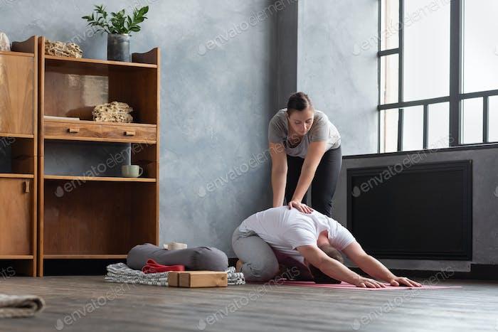 Кавказская учительница йоги помогает растянуть мышцы своего ученика.