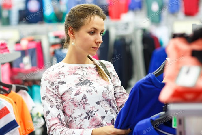 Woman choosing sweater during shopping at clothing shop