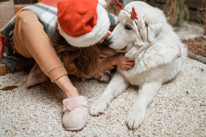 Woman celebrating with dog a New Year holidays at home