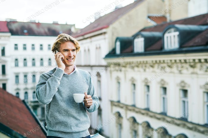 Young man with smartphone standing on a balcony in city, making a phone call.