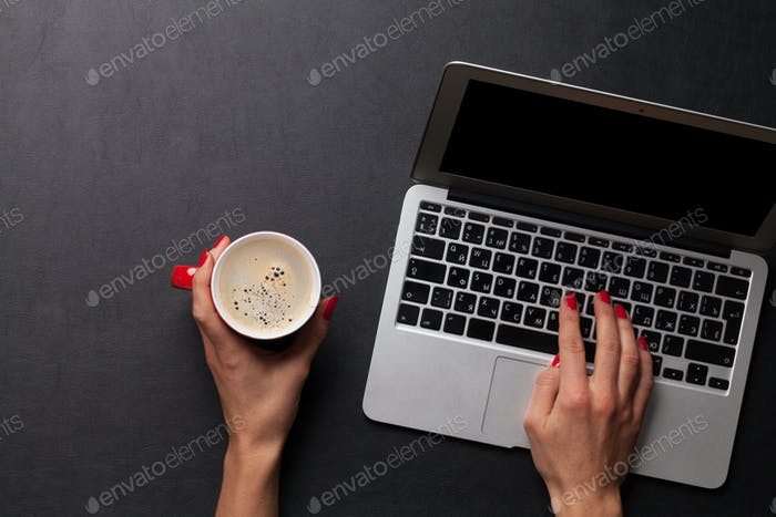 Female working on laptop with coffee cup