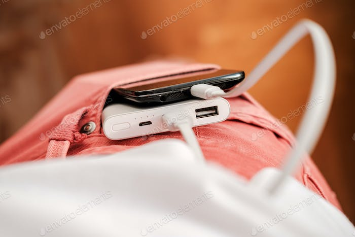 Power bank and a mobile phone that is charging lies in the front pocket of coral-colored jeans