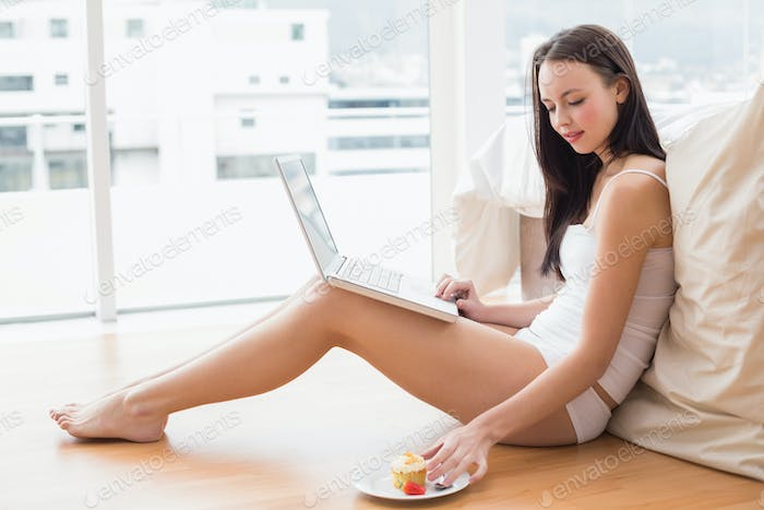Pretty brunette using laptop sitting on floor at home in the bedroom