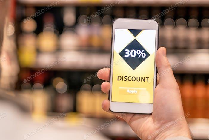 Mano del cliente masculino envejecido contemporáneo con smartphone usando descuento