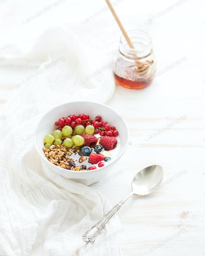 Healthy breakfast. Bowl of oat granola with yogurt, fresh berries and honey.