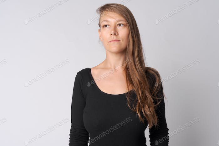 Face of young beautiful businesswoman thinking and looking up