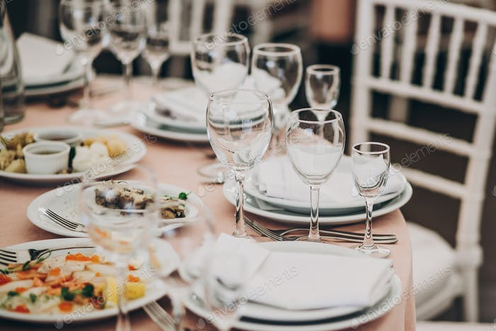 Wedding setting, tender pink table with glasses, cutlery, napkin and delicious food and drinks