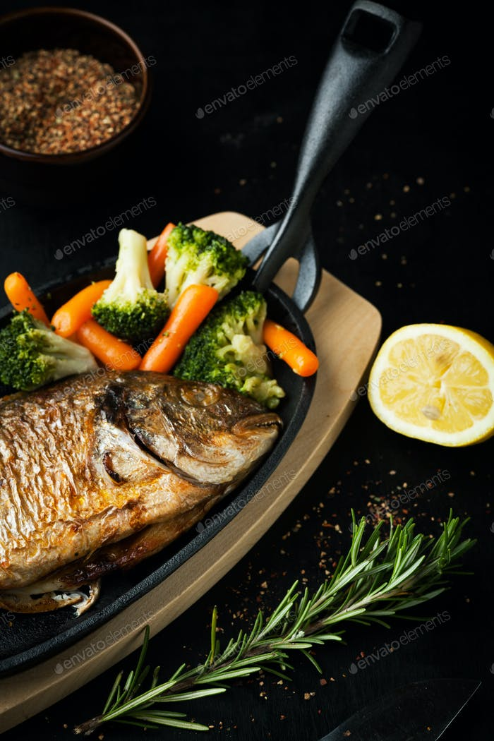 Baked fish with vegetables and lemon