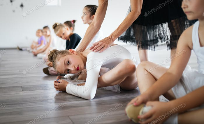 Ballet teacher and students ballerinas exercising in dance class in school