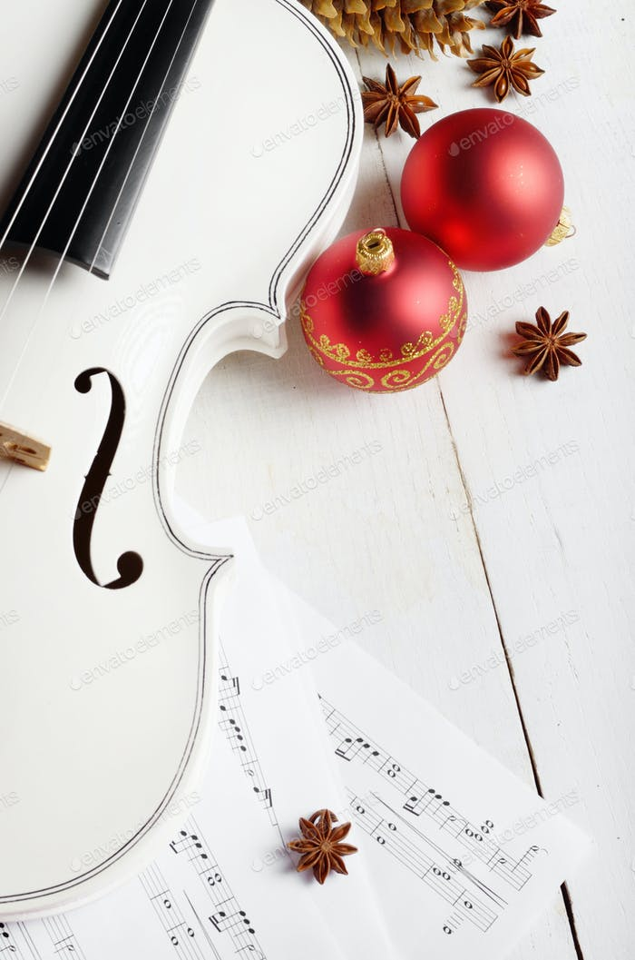 Close view of a violin musical notes and red christmas decoratio