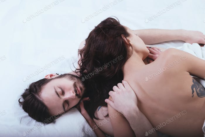 Beautiful loving couple is posing in a bed