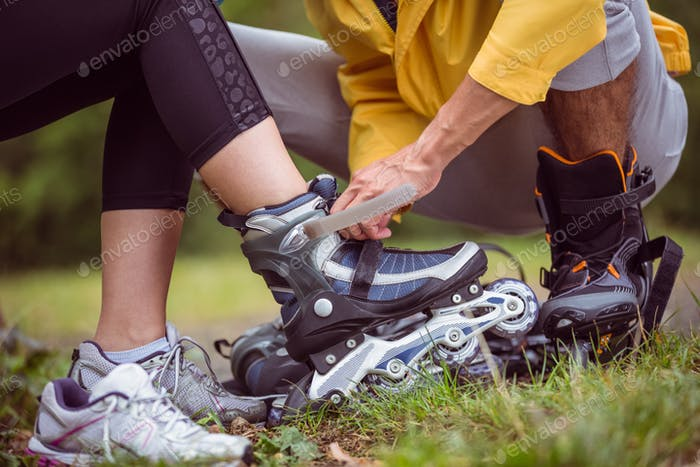 Happy couple putting on roller blades in the countryside