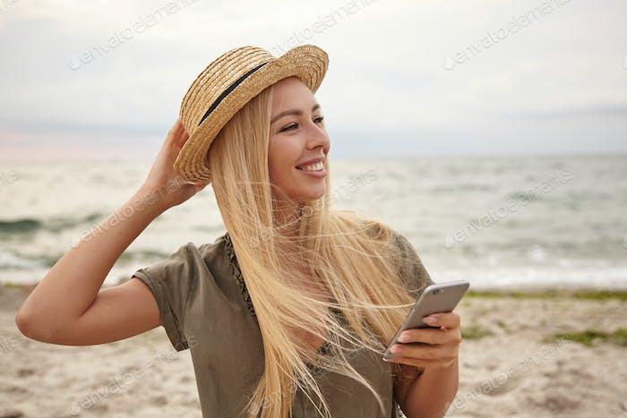 Nahaufnahme einer schönen blonden Frau mit lässiger Frisur, die am grauen bewölkten Tag über dem Meer posiert