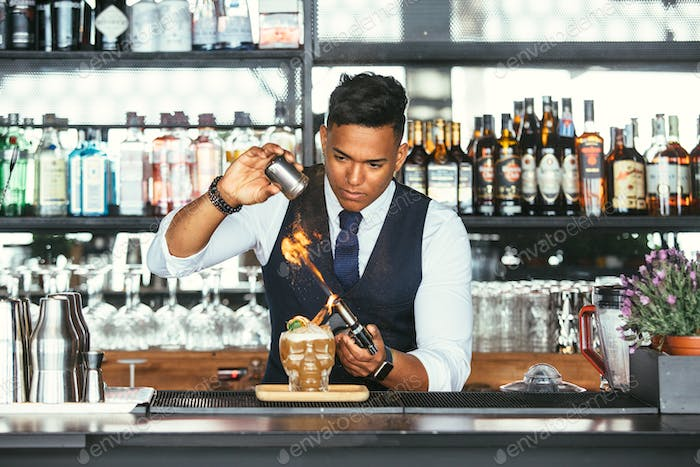 Concentrated expert bartender uses a blowtorch for a cocktail
