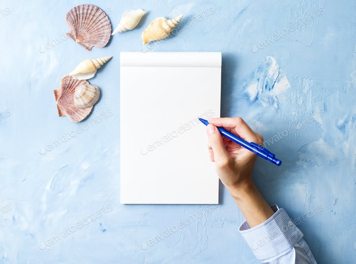 woman writes in notebook on stone blue table, Mock up with frame of seashell, top view