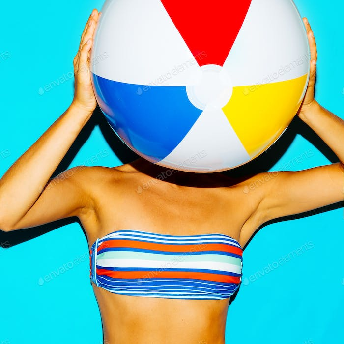 Tanned girl in a stylish bikini and with a beach ball. Beach sty