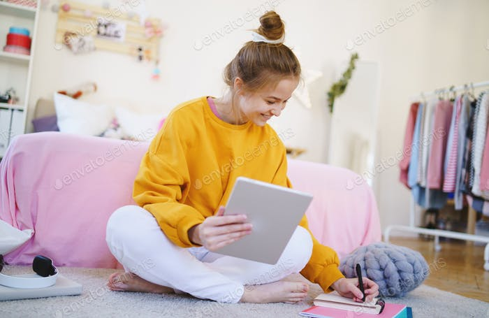Young girl with tablet sitting on floor, studying during quarantine
