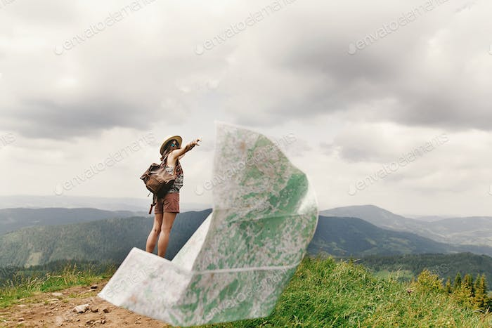 Stylish traveler hipster woman losing map on top of mountains and sky