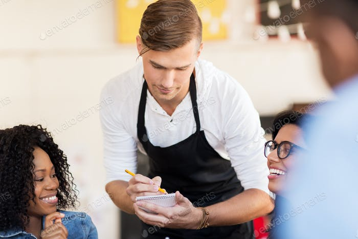 customers and waiter with notepad or restaurant