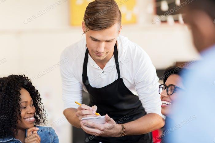 клиенты и официант с блокнотом или рестораном