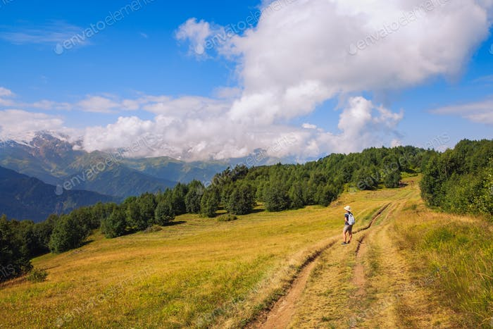 Woman hiker admiring mountains and meadows, Svaneti, Georgia