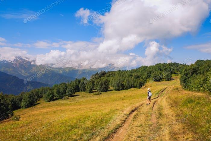 Woman hiker admiring mountains and meadows, Svaneti, Georgia