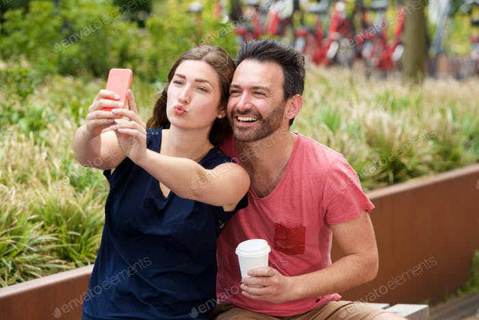 Happy young couple sitting together taking selfie on smart phone