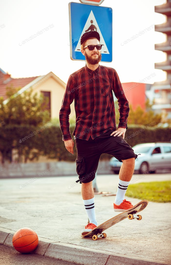 Young man in sunglasses with a skateboard on a street in the cit