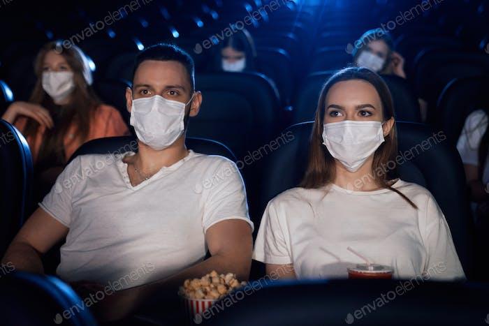 Dulce pareja usando máscaras en el cine