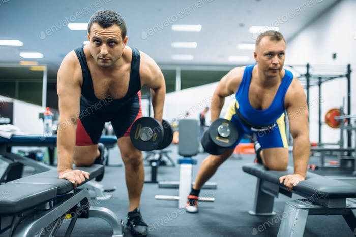 Two weightlifters doing exercise with dumbbells